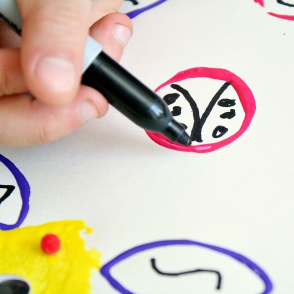 Adding details to bug art with permanent marker