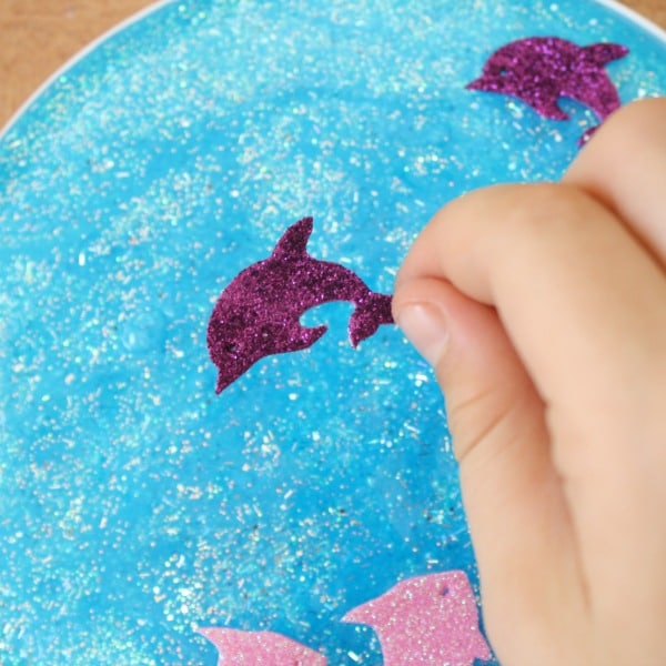 Adding ocean stickers to preschool suncatcher