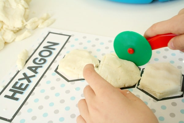 Cutting play dough shapes with snowman shape mats