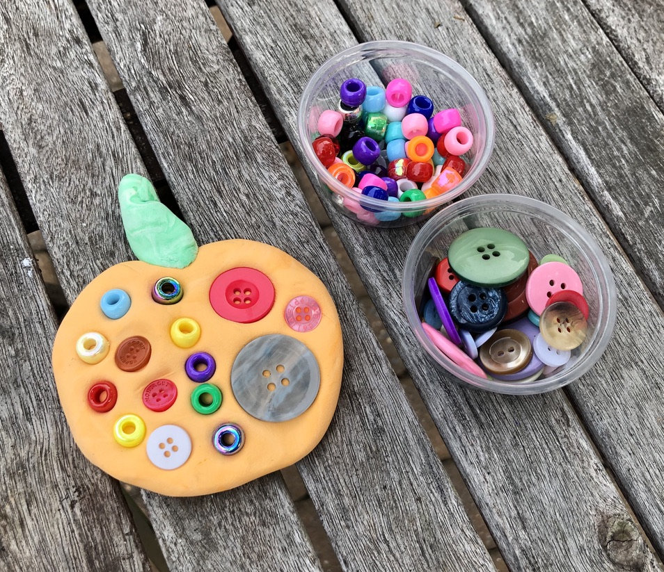 beads and buttons on a clay pumpkin