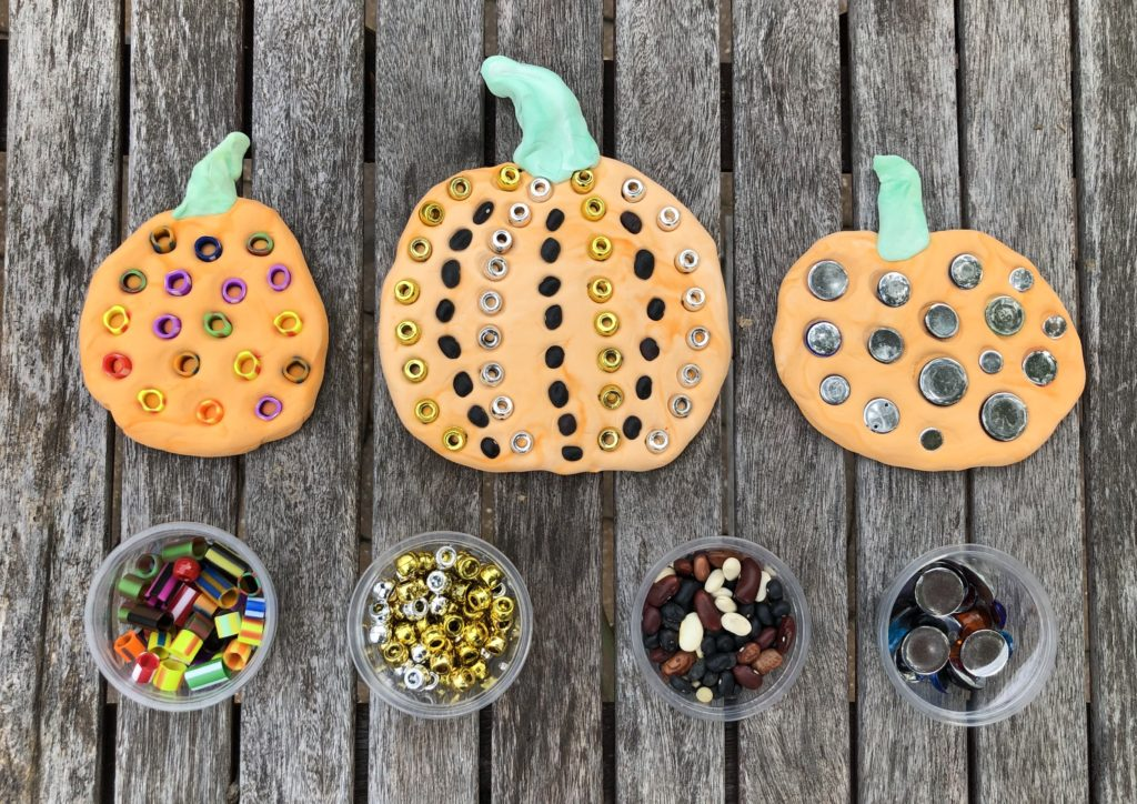 three clay pumpkins dotted with beads